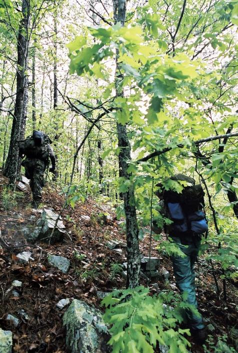 Colyer and Higgins scale a rugged mountain slope in the Ouachita Mountains as they seek out sites for camera traps. Photo: Chris Buntenbah.