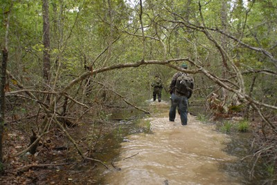 Daryl Colyer leads Travis Lawrence and the rest of the team through a creek in Area Y to avoid the nearly impenetrable thicket to either side.